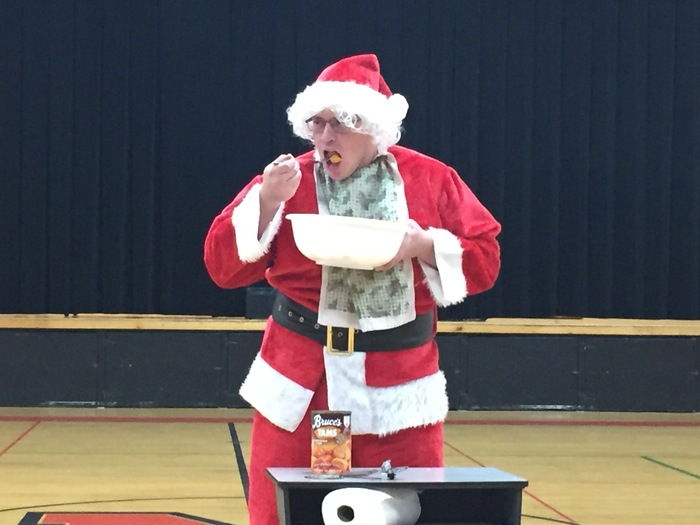 a male teacher dressed as Santa eating a large bowl of yams