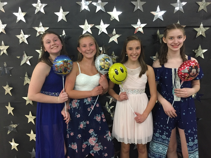 Four girls with balloons smiling for picture