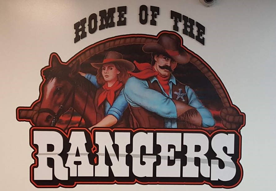 Cowboy and cowgirl with rangers sign